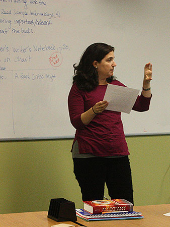 A woman stands in front of a whiteboard gesturing as she teaches