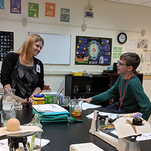 A teacher smiles at a student in a science lab