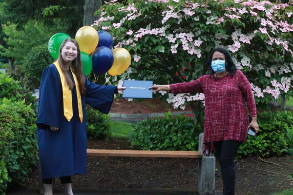 A graduate in gown and stole receives her diploma from the Head of School, who is wearing a face mask.